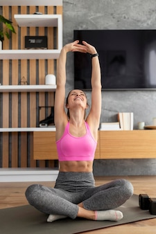 Full shot mulher meditando dentro de casa