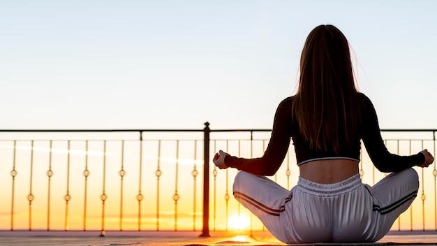 Full shot mulher meditando do lado de fora