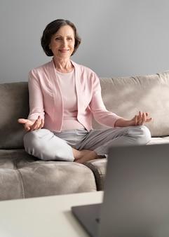 Full shot mulher meditando em casa