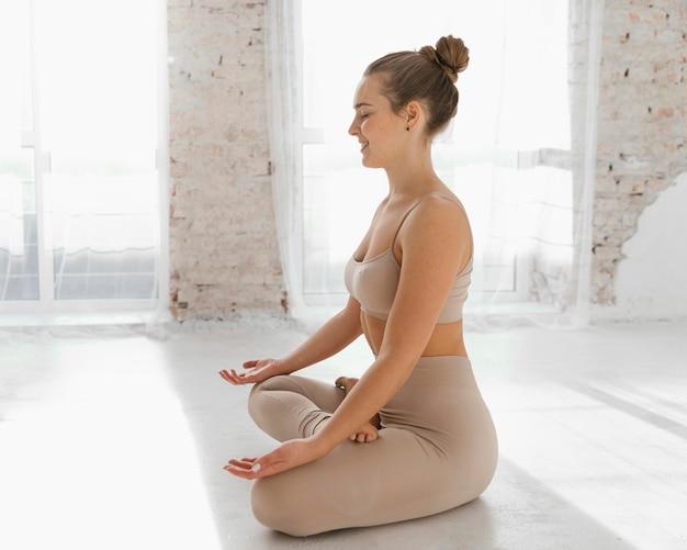 Full shot mulher meditando vista lateral
