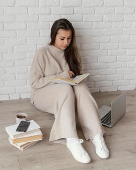 Full shot mulher no chão lendo
