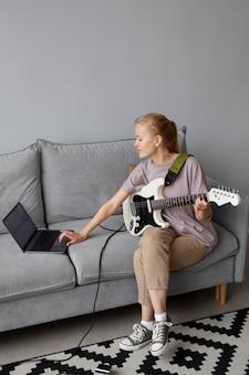 Full shot mulher no sofá com guitarra