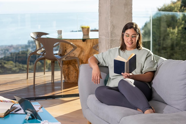 Full shot mulher no sofá lendo