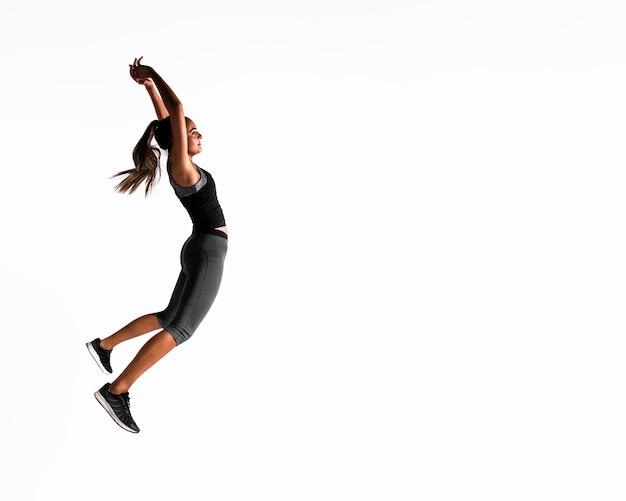 Full shot mulher pulando dentro de casa