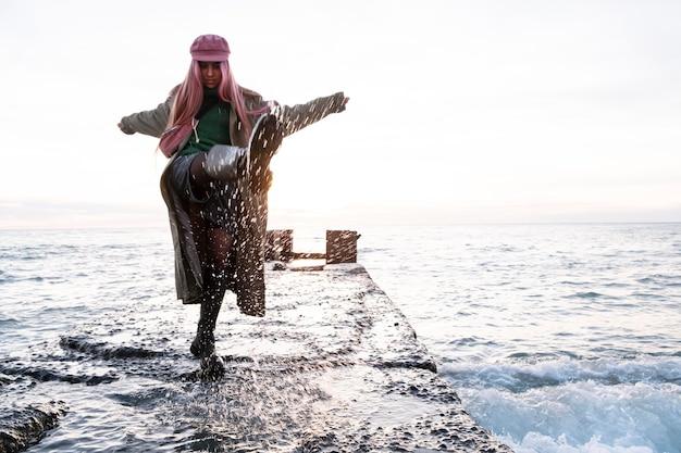 Full shot mulher se divertindo à beira-mar
