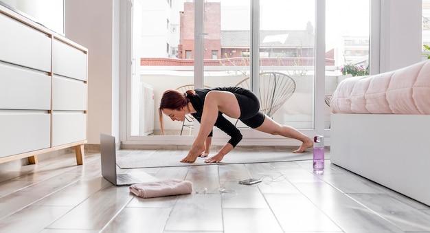Full shot mulher se exercitando com laptop