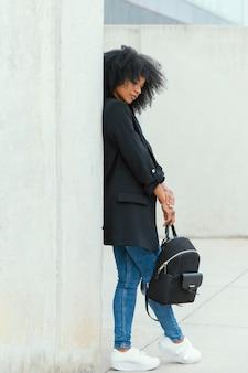 Full shot mulher segurando mochila