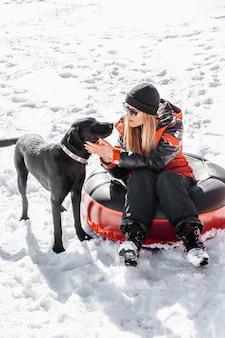 Full shot mulher sentada ao ar livre com um cachorro fofo