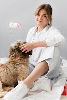 Full shot mulher sentada com um cachorro fofo