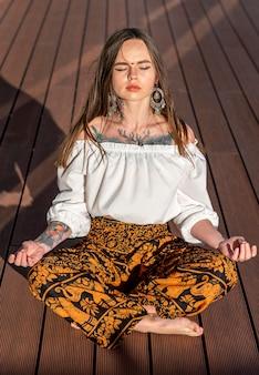 Full shot mulher sentada e meditando