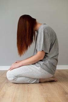 Full shot mulher sentada no chão