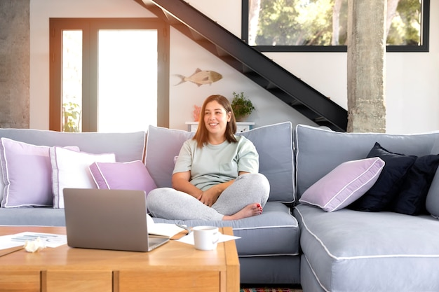 Full shot mulher sentada no sofá