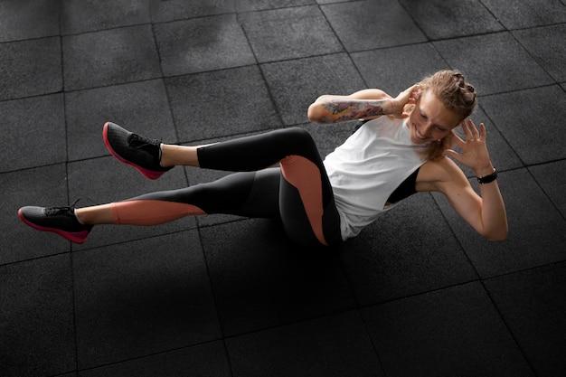 Full shot mulher treinando abdominais na academia