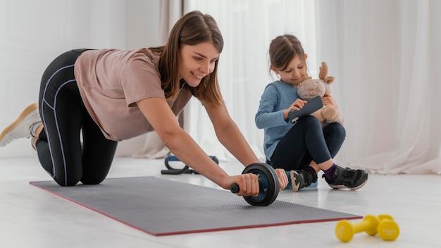 Full shot mulher treinando dentro de casa