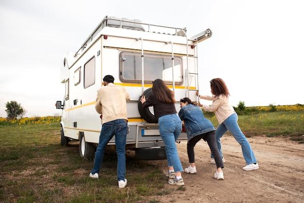 Full shot pessoas empurrando campervan