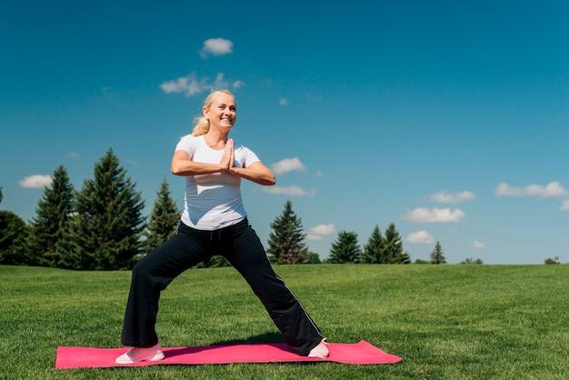 Full shot smiley mulher exercício ao ar livre