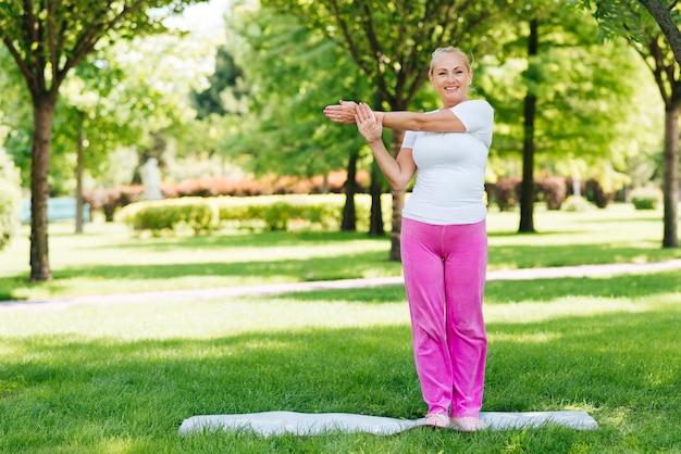 Full shot smiley mulher exercitando na natureza