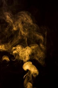 Fumaça amarela abstrata no fundo preto