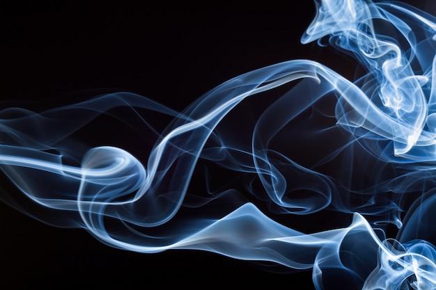 Fumaça azul sobre fundo preto, movimento abstrato, conceito de escuridão