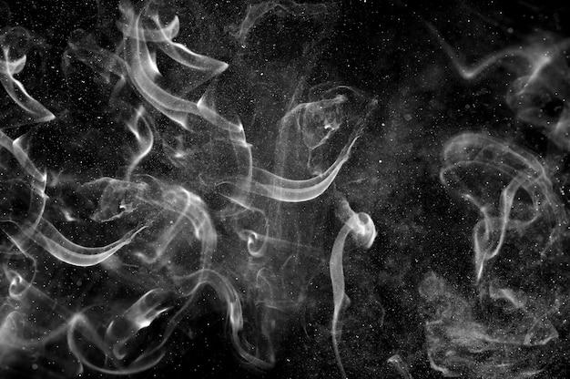 Fumaça branca abstrata e spray de água em um fundo preto