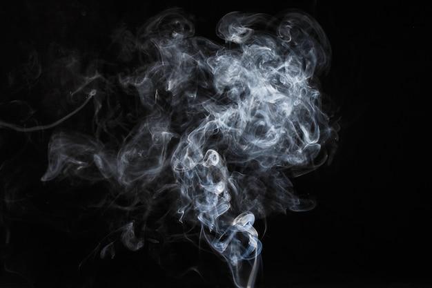 Fumaça branca abstrata isolada em fundo escuro