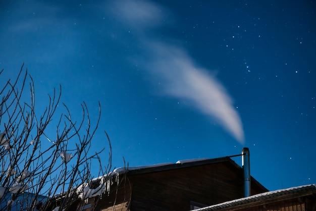Fumaça branca da chaminé da casa para o fundo do céu noturno de inverno com muitas estrelas.