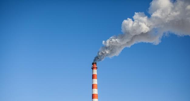 Fumaça branca espessa saindo da chaminé da sala da caldeira. fuma contra o céu azul. poluição do ar. aquecimento da cidade. zona industrial.