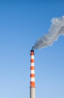 Fumaça branca espessa saindo da chaminé da sala da caldeira.