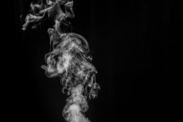 Fumaça branca na parede preta. imaginei fumaça em uma parede escura.