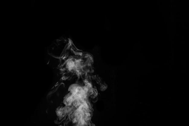 Fumaça branca sobre fundo preto. imaginei fumaça em um fundo escuro. fundo abstrato, elemento de design, para sobreposição em imagens