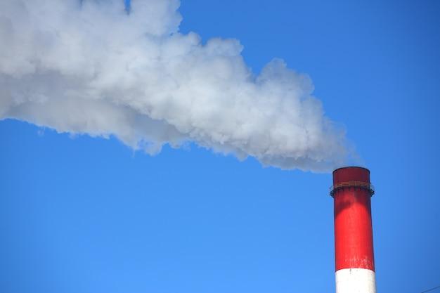 Fumaça branca vem de canos contra o céu azul