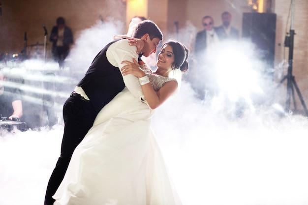 Fumaça circunda casal de noivos dançando no hall