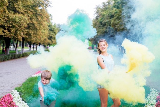 Fumaça colorida e crianças. fumaça de festa verde e amarela brilhante. aniversário ou festa. as crianças se divertem, riem e correm. feliz verão brilhante.