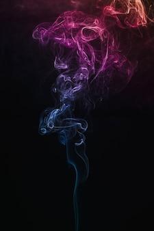 Fumaça colorida flutuando no ar em fundo escuro