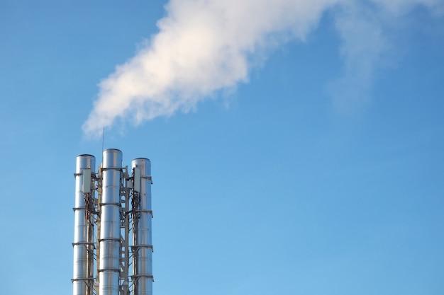 Fumaça dos canos contra o céu azul