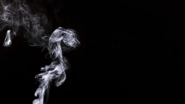 Fumaça girando em branco sobre fundo preto