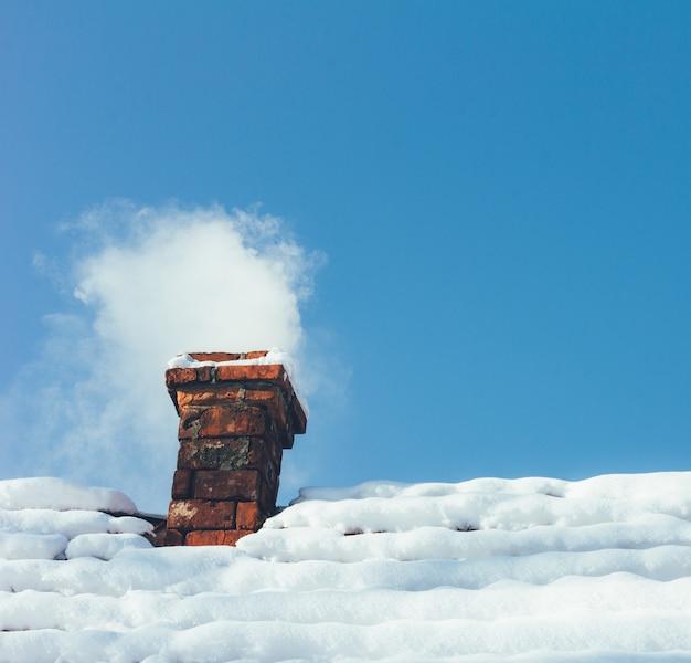 Fumaça saindo de uma chaminé de tijolos em uma casa coberta de neve com céu azul