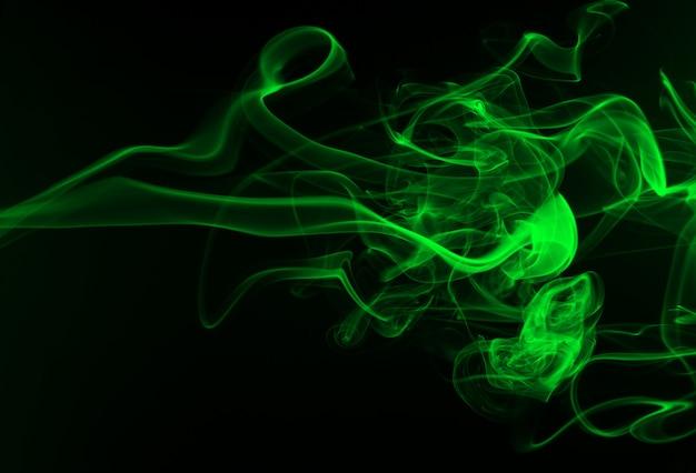 Fumaça verde abstrata no fundo preto, conceito da escuridão