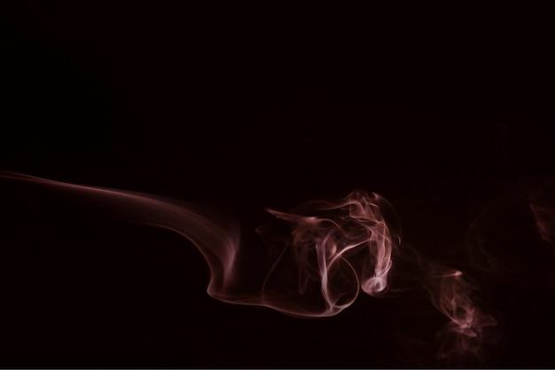 Fumaça vermelha escura soprando contra fundo preto