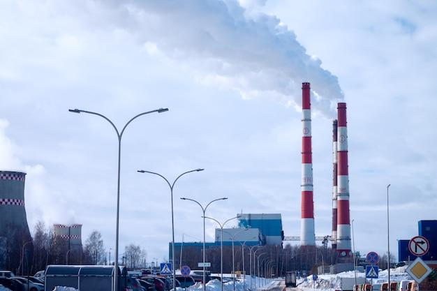 Fumando chaminés de fábrica, no fundo do céu com nuvens na cidade