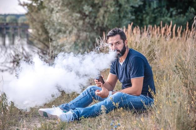 Fumante elegante e brutal exalando vapor de um cigarro eletrônico ao ar livre