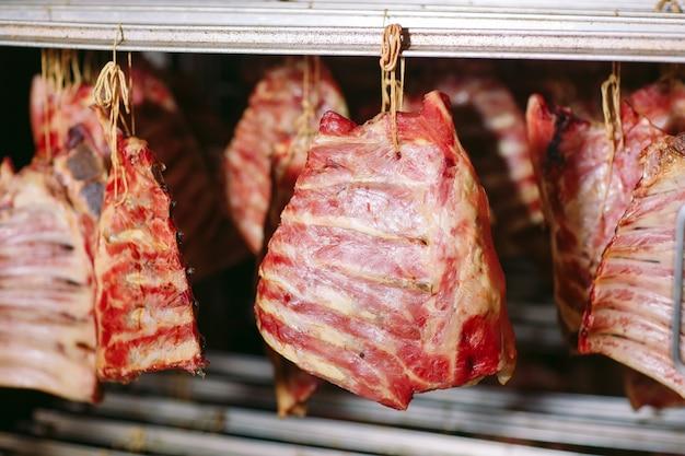 Fumar carne no fumeiro.