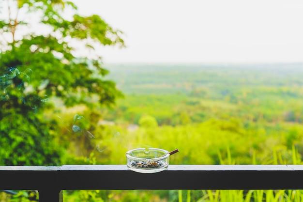 Fumar cigarro não é bom para a saúde no cinzeiro na varanda.