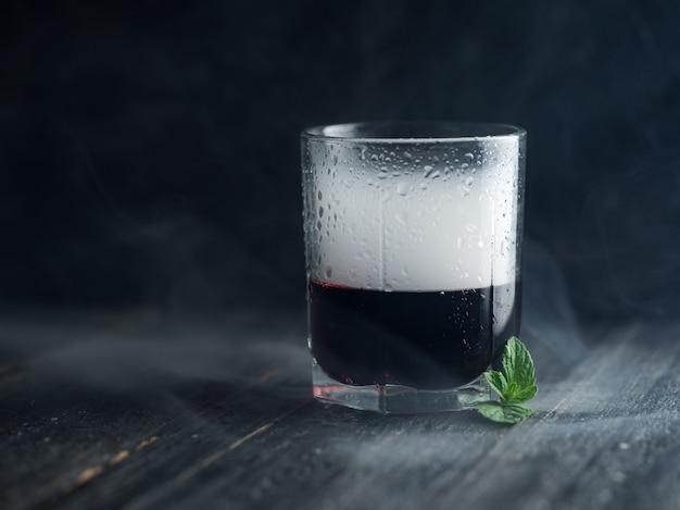 Fume em um copo com álcool vermelho