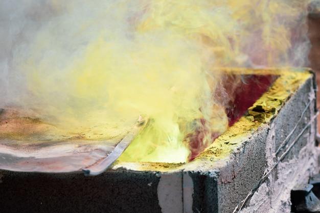 Fume o ouro derretido que está sendo derramado na estátua de buddha em tailândia.