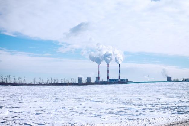 Fumegando chaminés de uma fábrica em um fundo de céu azul com nuvens e neve branca