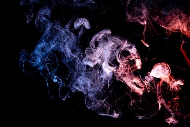 Fumo azul e vermelho da bomba no preto isolado