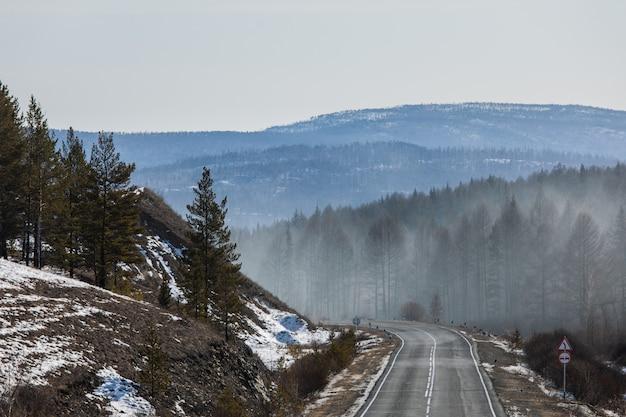 Fumo da floresta do fogo. vista da estrada da montanha de inverno