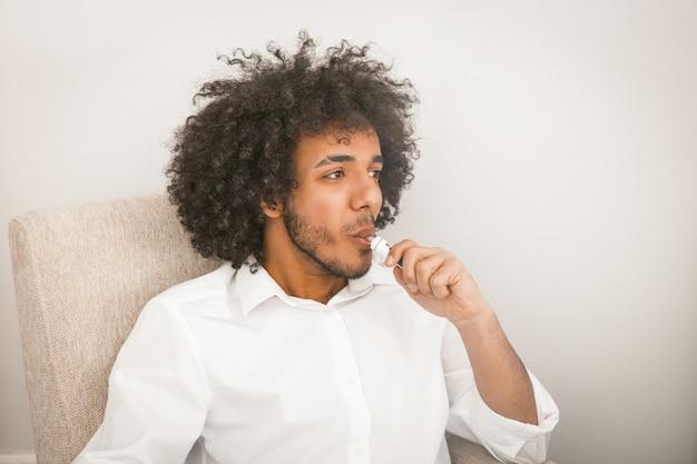 Fumo novo do homem de negócios do cigarro eletrônico que olha lateral com cpase do spacepace ou da cópia. cara árabe bonito vestindo camisa branca senta-se no fundo da parede branca. imagem enfraquecida