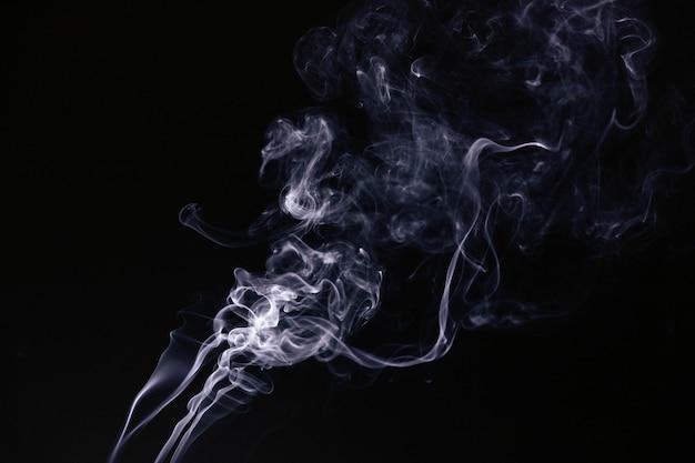 Fumo ondulado branco sobre fundo preto